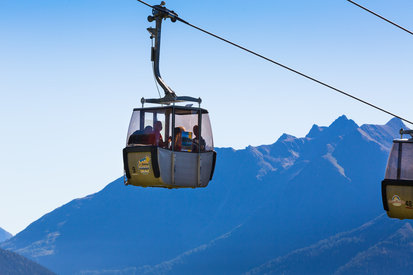 Families with children take a trip on the cable cars in Kappl