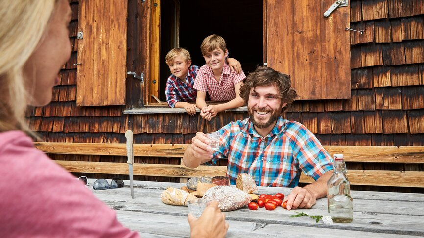 Family enjoys their snack at a rustic mountain hut