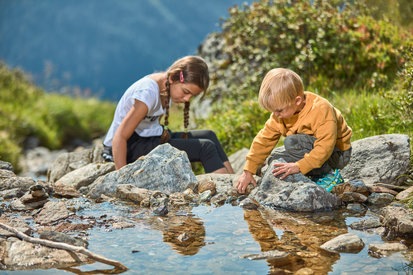 Children play at the brook in the mountain landscape of Kappl