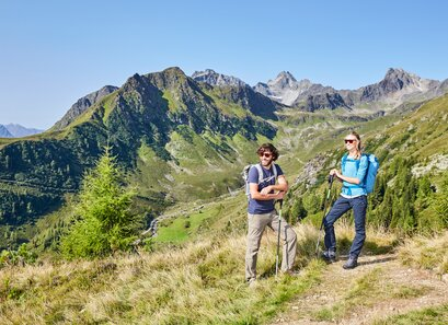 Hikers enjoy the view of the mountain landscape in Kappl