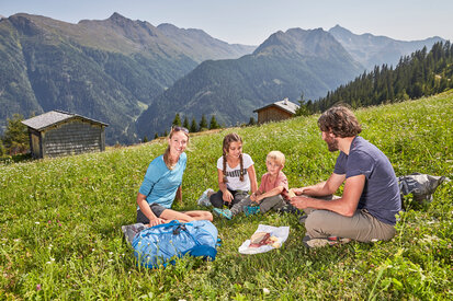 Family enjoys a picnic in the hiking paradise Kappl