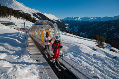 Children are waiting on the conveyor belt for their skiing experience in the beginner area of the ski area Kappl